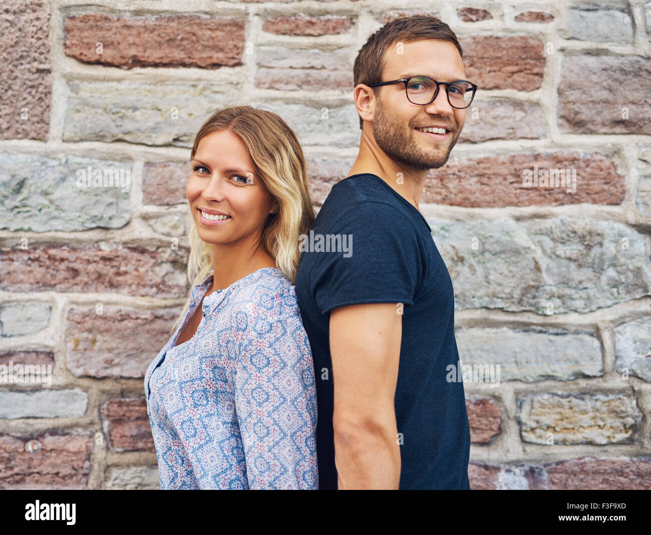 Happy Couple Standing Back to Back and Smiling at the Camera Against Brick Wall Background - Stock Image