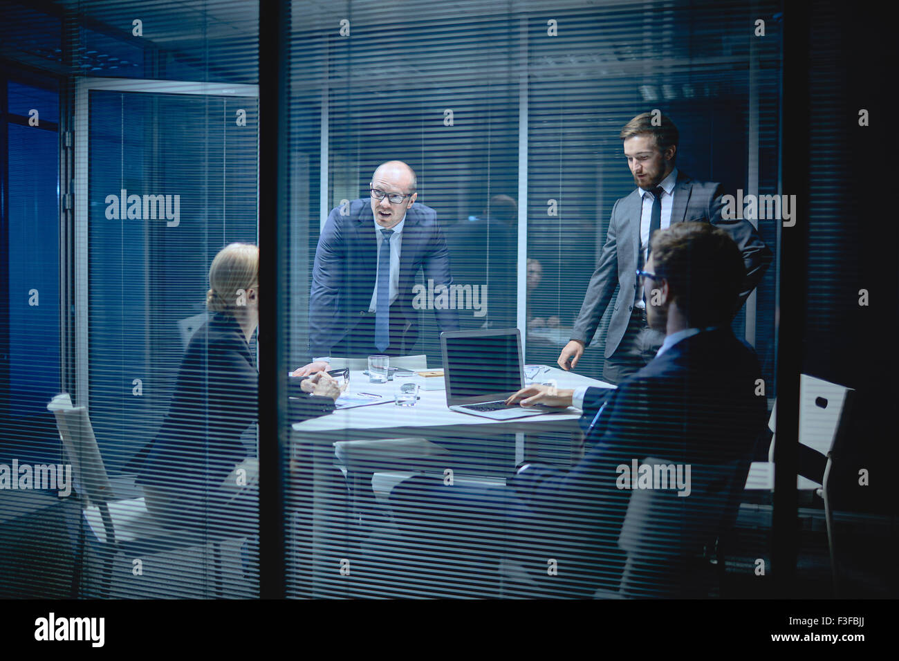 Group of co-workers discussing ideas at meeting in office - Stock Image
