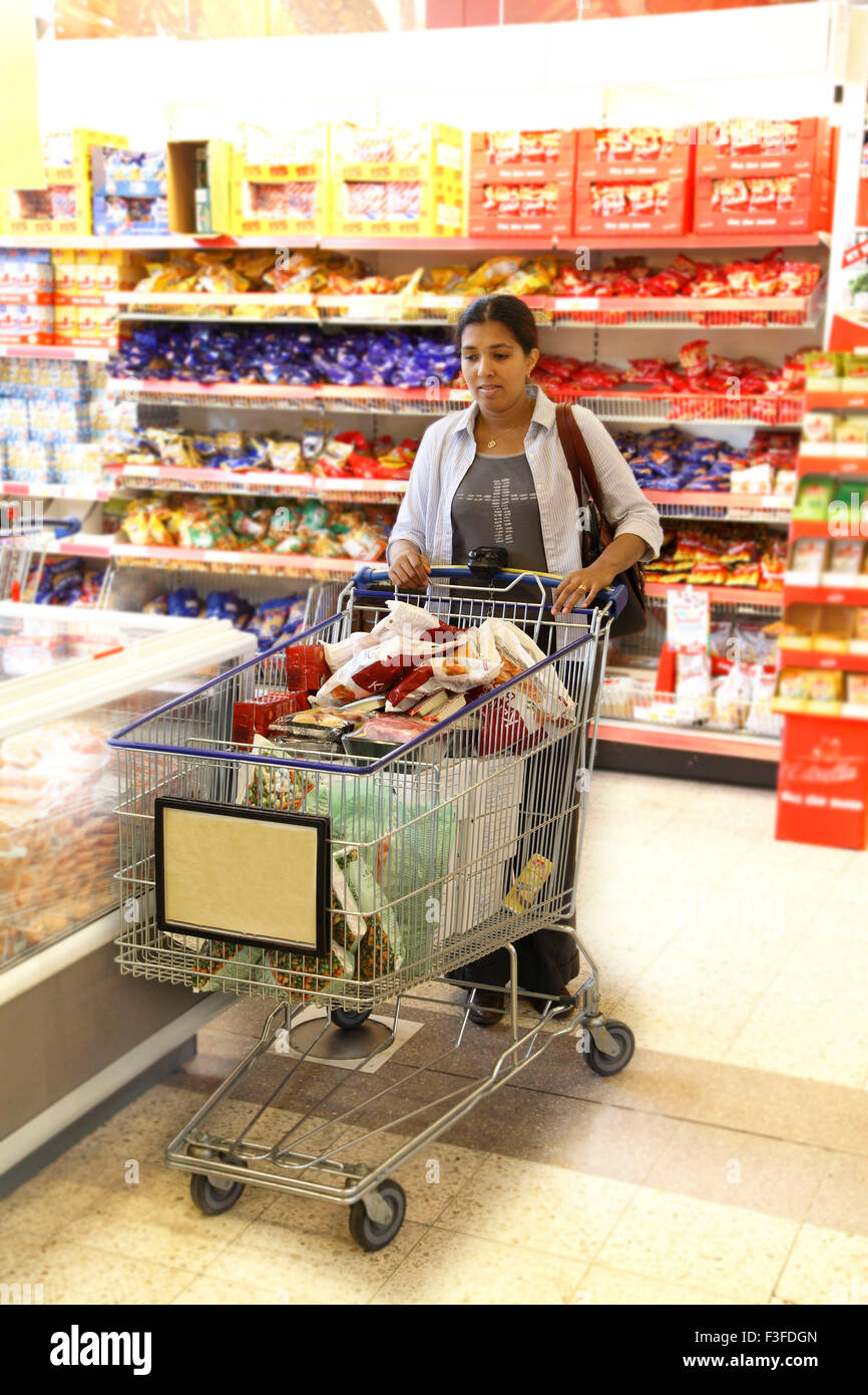 Indian lady buying trolley load of consumable goods from Mall shop in Sweden MR#468 NO PROPERTY RELEASE - Stock Image