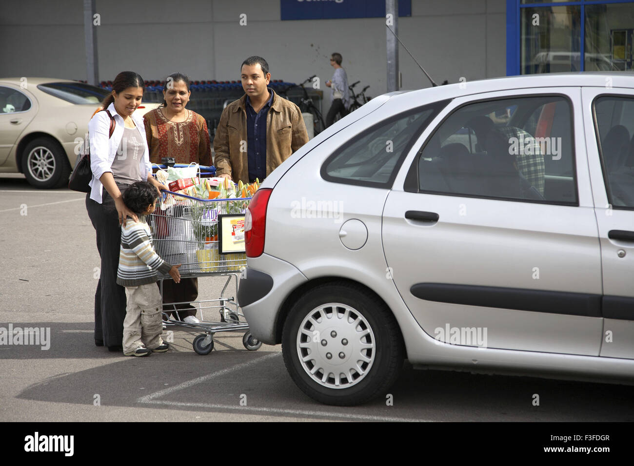 Family keeping consumable items from trolley to car boot ; Sweden MR#468 - Stock Image