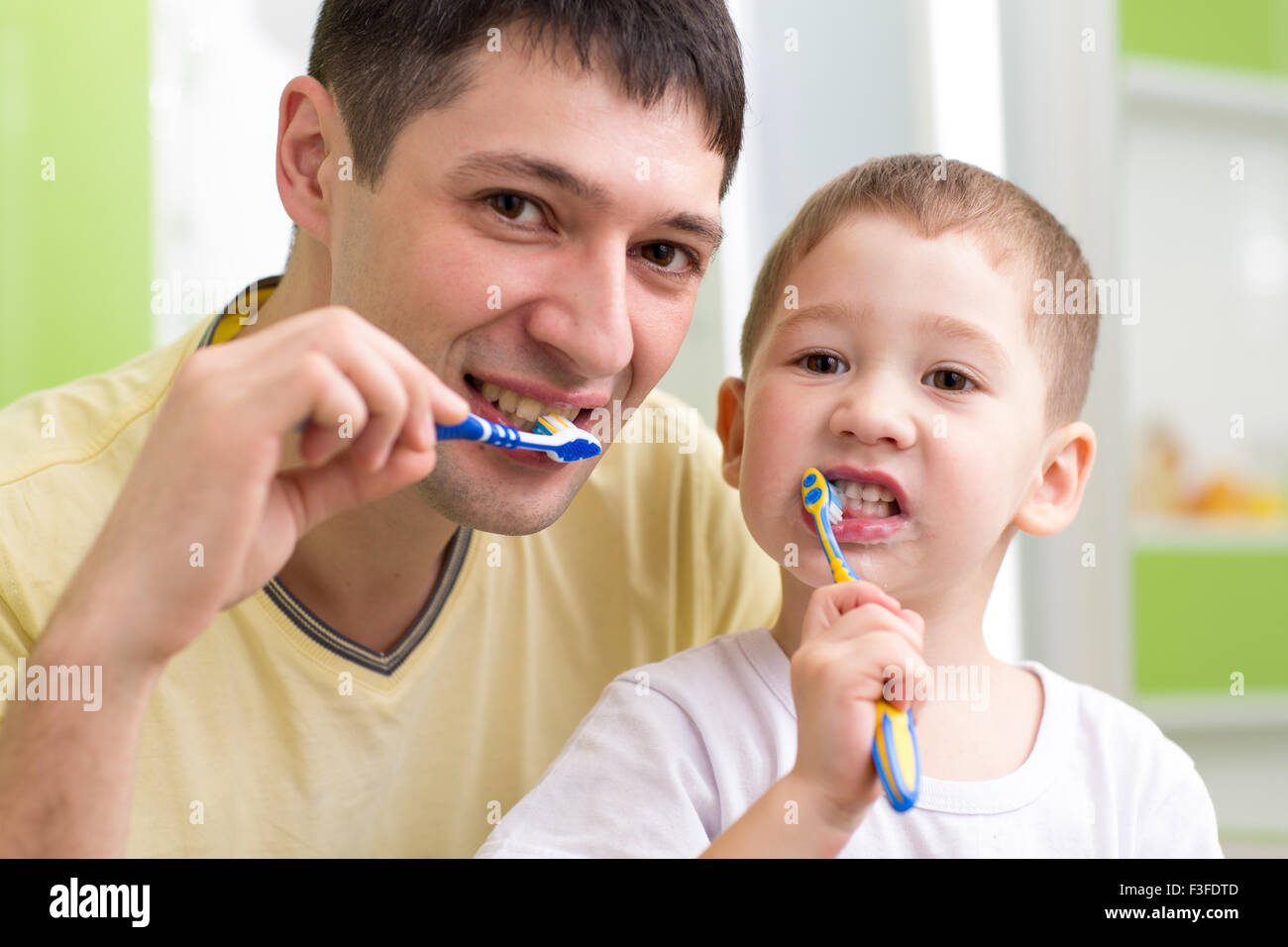 child and his father brushing teeth in bathroom - Stock Image