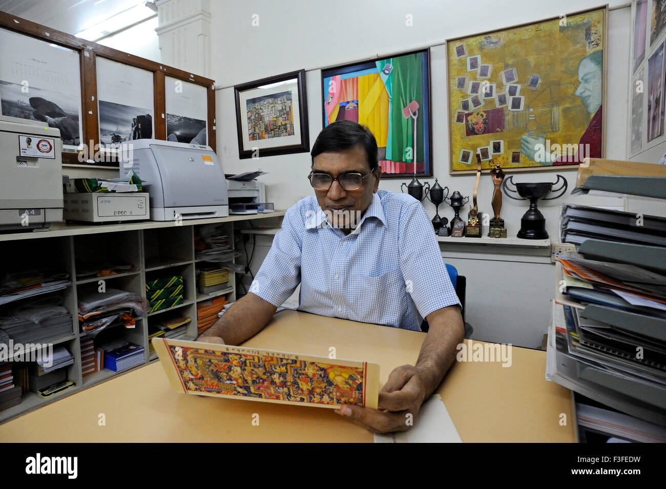 Jagdish Agarwal founder of Dinodia Picture Library sitting in Kalbadevi office with fax machine photo copier awards Stock Photo