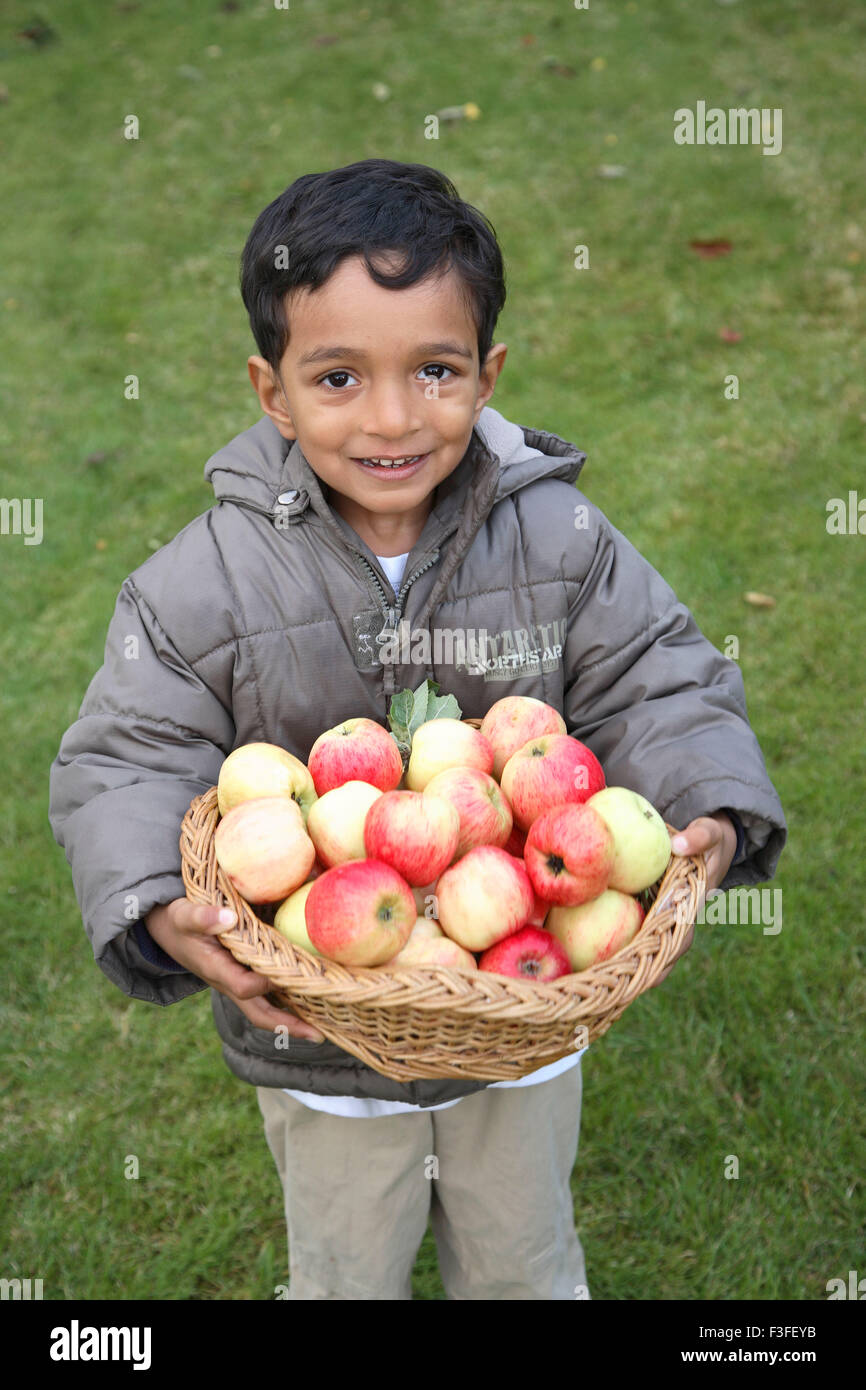 Four year old boy holding basket full of red apples MR#468 - Stock Image