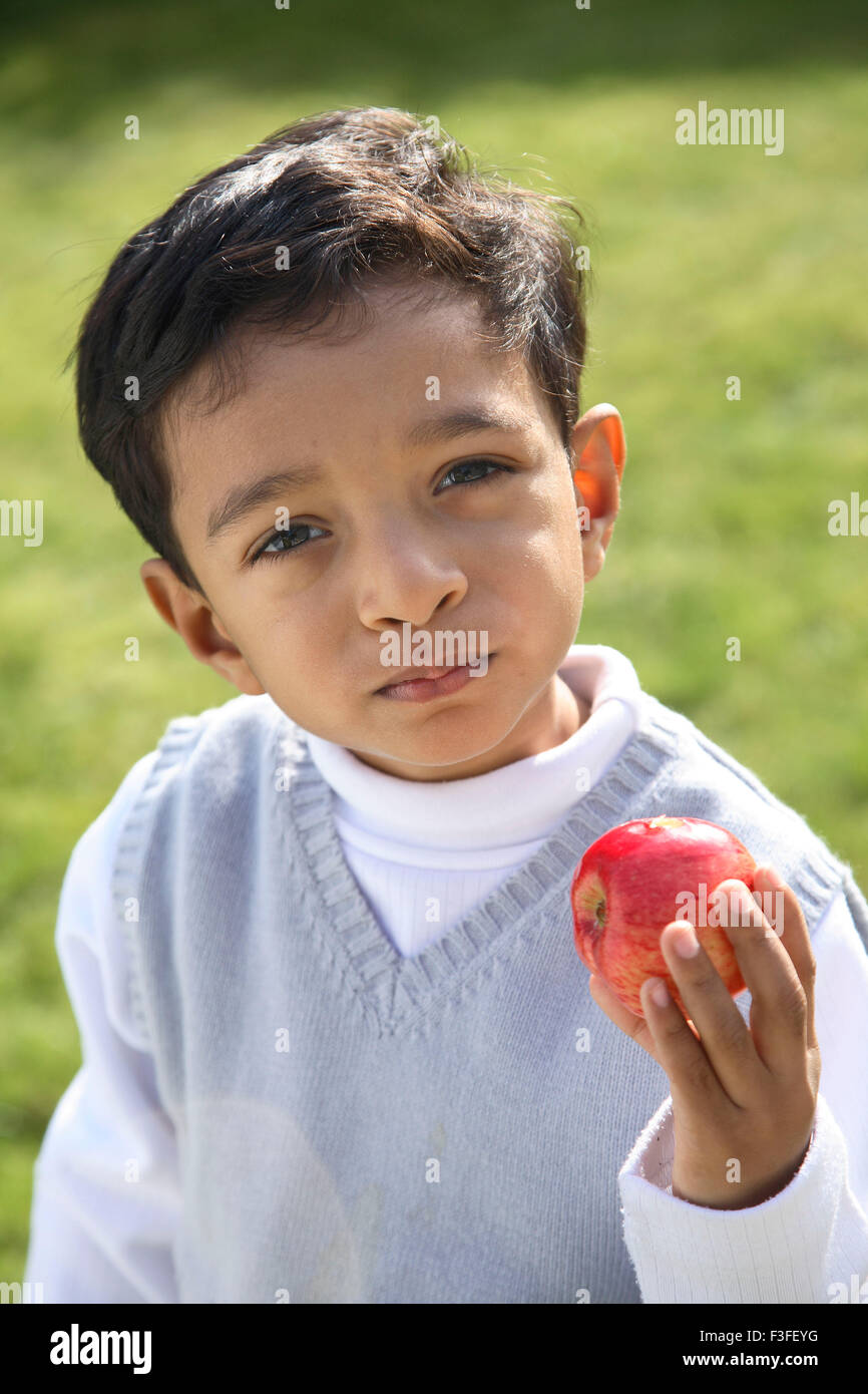Four year old boy holding red apple in hand MR#468 - Stock Image