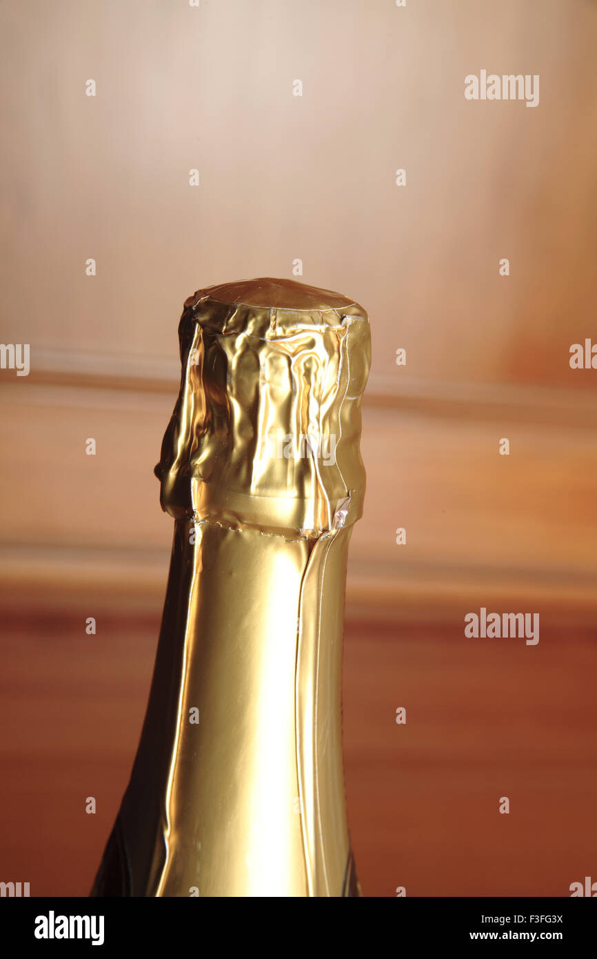 Sealed with golden foil Top of champagne bottle - Stock Image