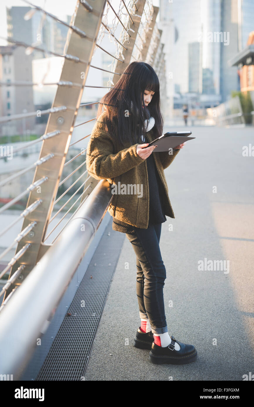 young beautiful asiatic long brown straight hair woman using a tablet connected online in the city during sunset - Stock Image