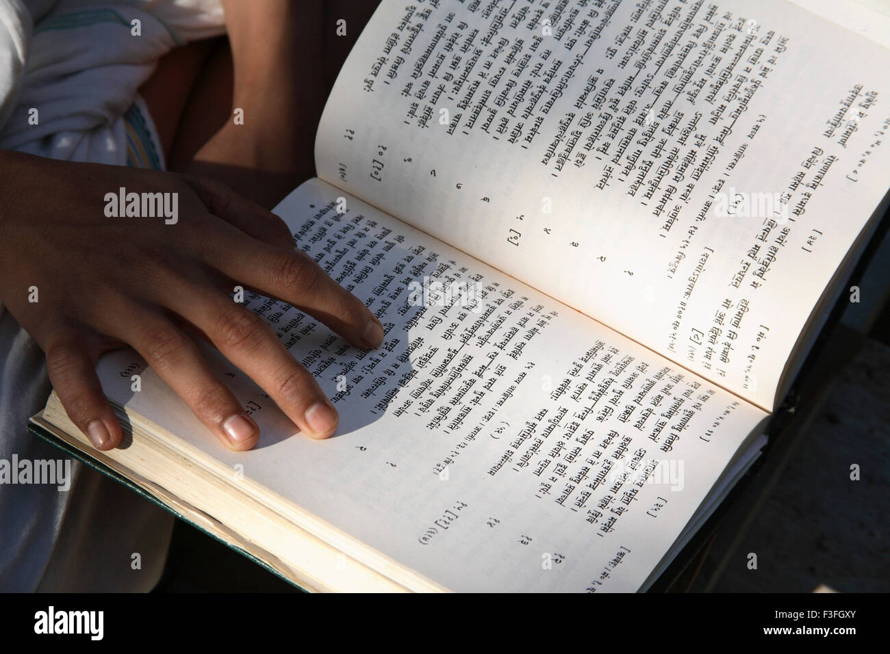 Young student of religious studies learning by heart Rugveda or Vedas studying other religious scriptures - Stock Image