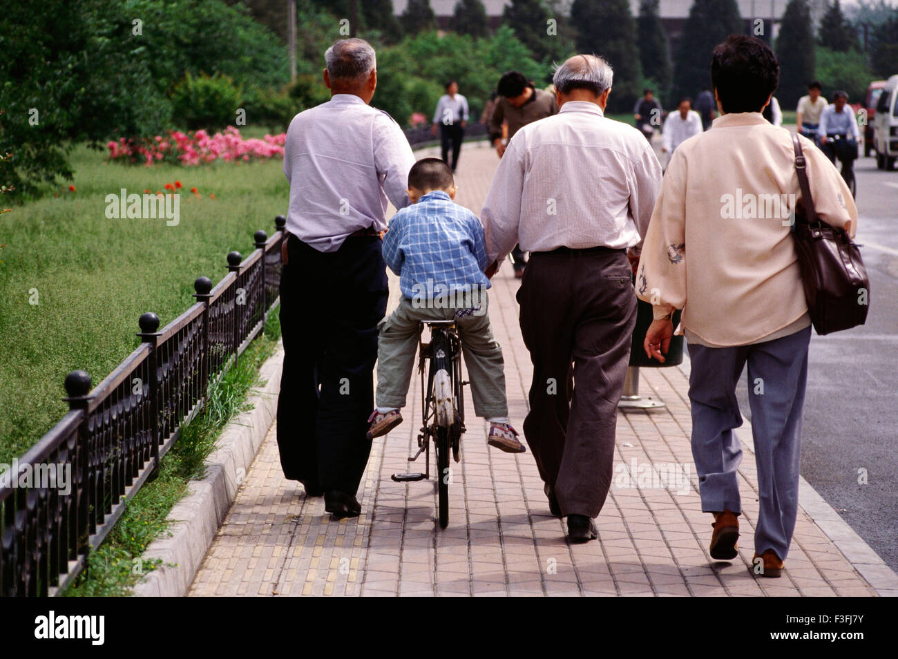 A kid gets driven around by his grand father on the streets of Beijing ; China - Stock Image
