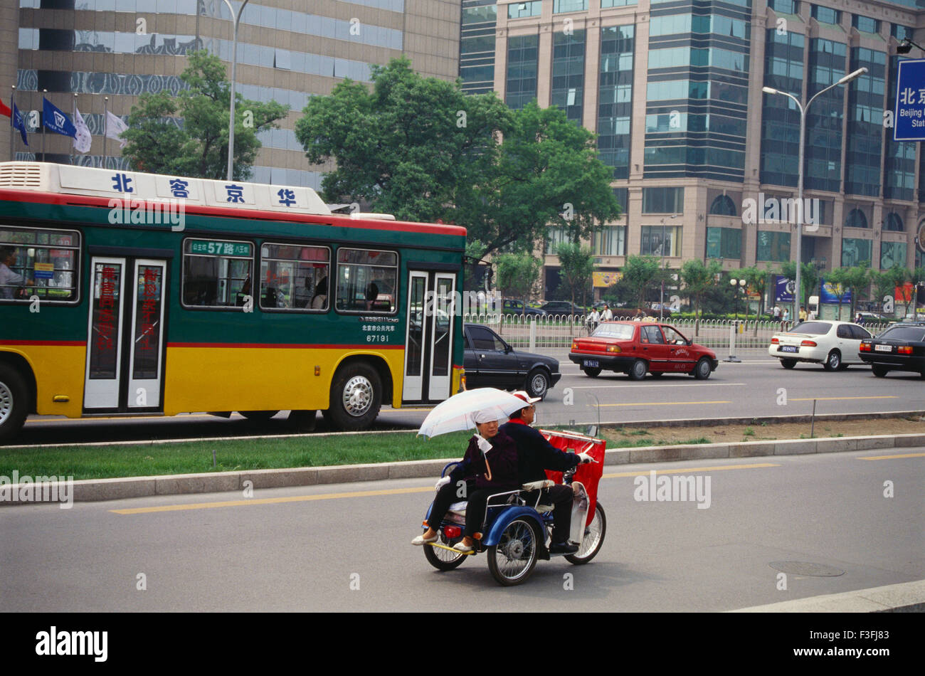A tri cycle being driven around in the city ; China - Stock Image