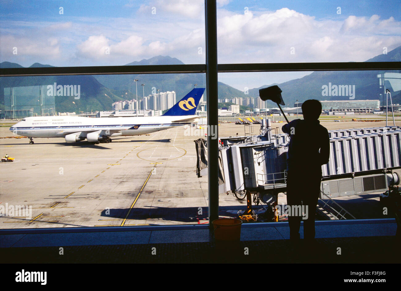 A Chinese worker cleans the window panes of Beijing airport ; China - Stock Image