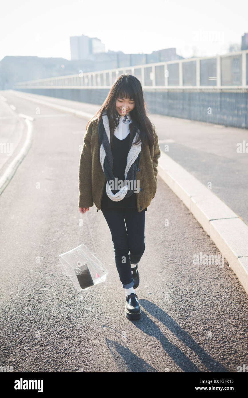 young beautiful asian hipster long brown straight hair woman walking in the city, looking downward smiling during - Stock Image