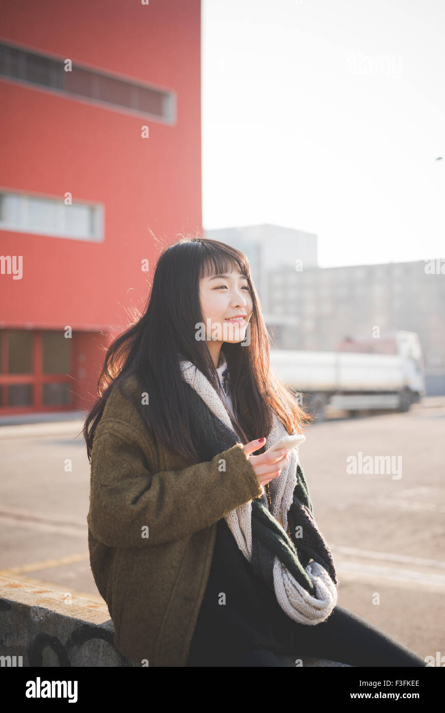 young beautiful asian hipster long brown straight hair woman sitting on a small wall, using a smartphone, overlooking - Stock Image
