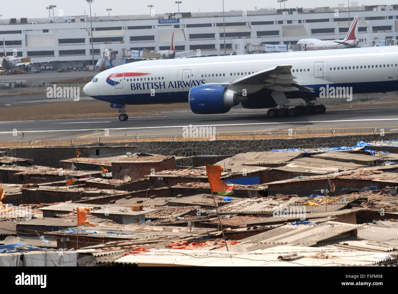 Commercial airliner preparing take off Sahar Airport Chatrapati Shivaji International Airport foreground slums airport - Stock Image