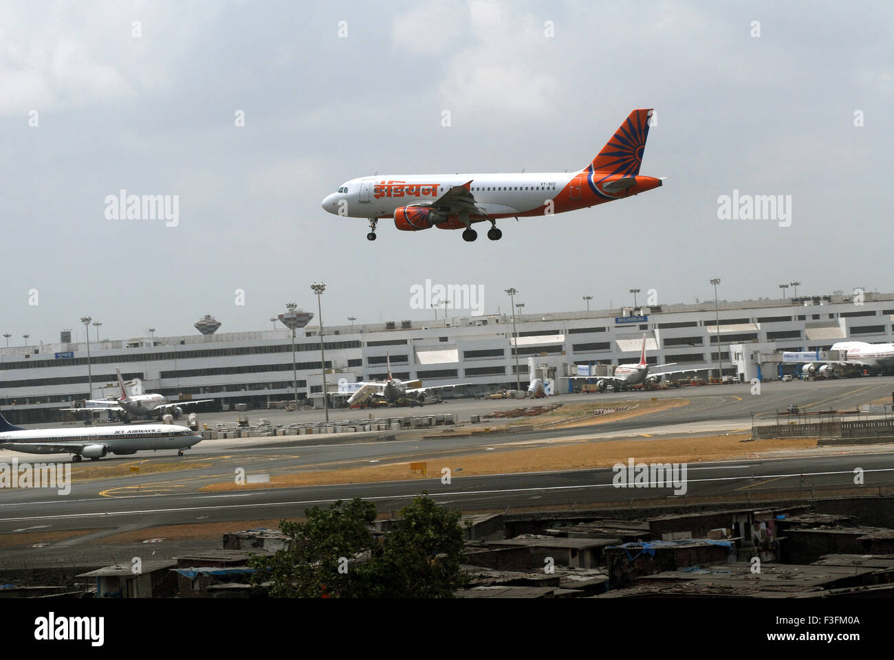Airlines commercial airliner preparing land Sahar Airport Chatrapati Shivaji International foreground slums airport - Stock Image