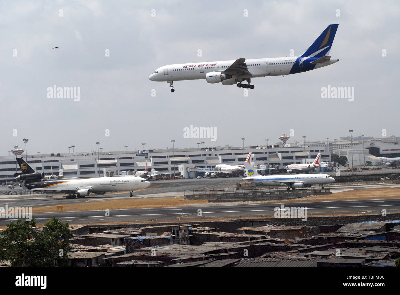 Airlines commercial airliner preparing land Sahar Airport Chatrapati Shivaji International Airport slum airport - Stock Image