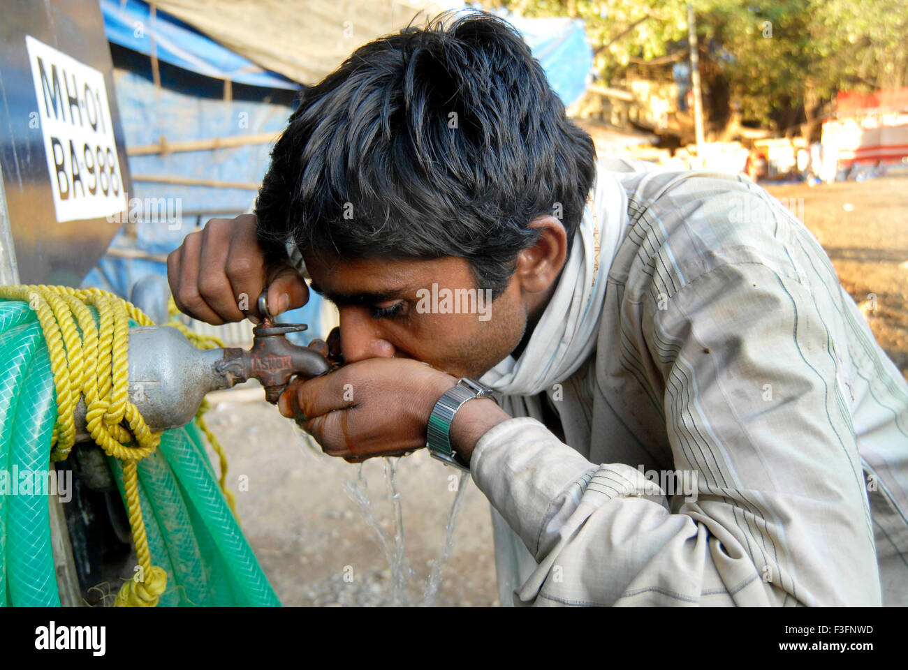 Man quenches his thirst by drinking water for tap ; Bombay Mumbai ; Maharashtra ; India - Stock Image