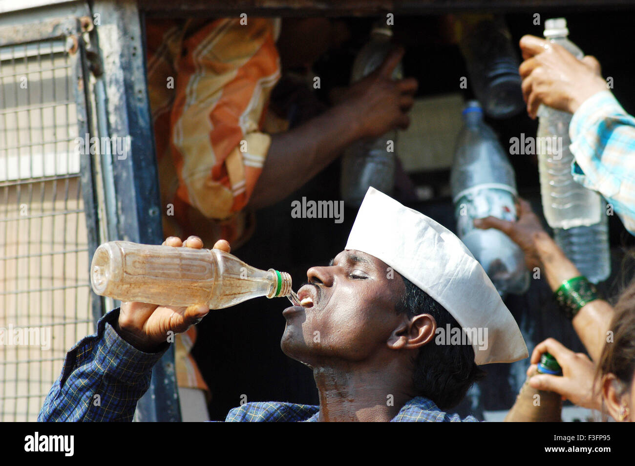 Man quench his thirst by drinking water form plastic bottle ; Bombay Mumbai ; Maharashtra ; India - Stock Image