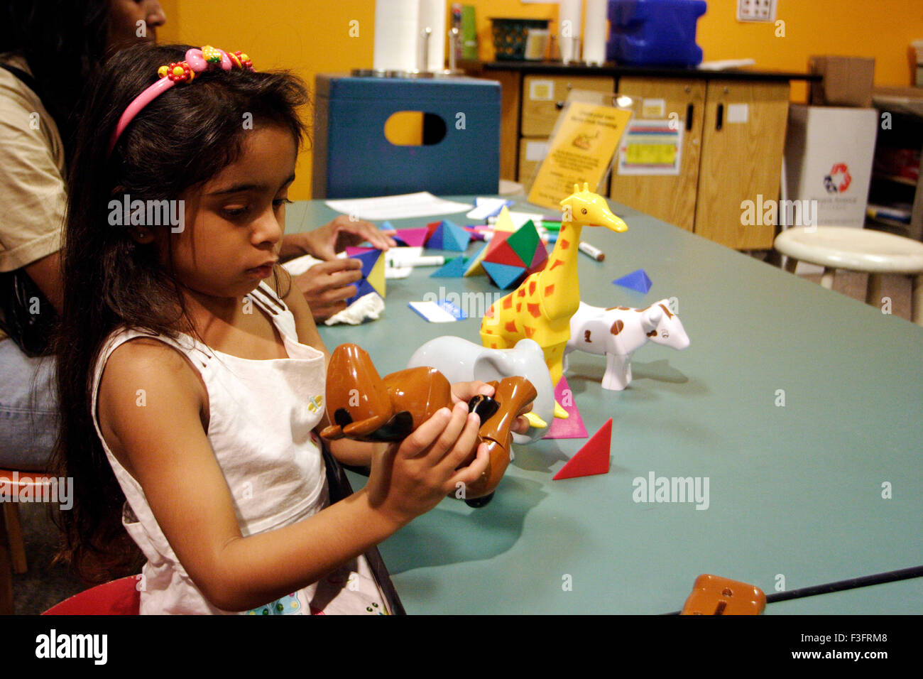 Girl trying to assemble toy in Denver Museum - Stock Image