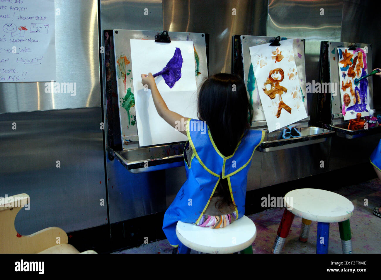 Girl wearing apron and took brush to paint continued for log time painting on paper in museum - Stock Image