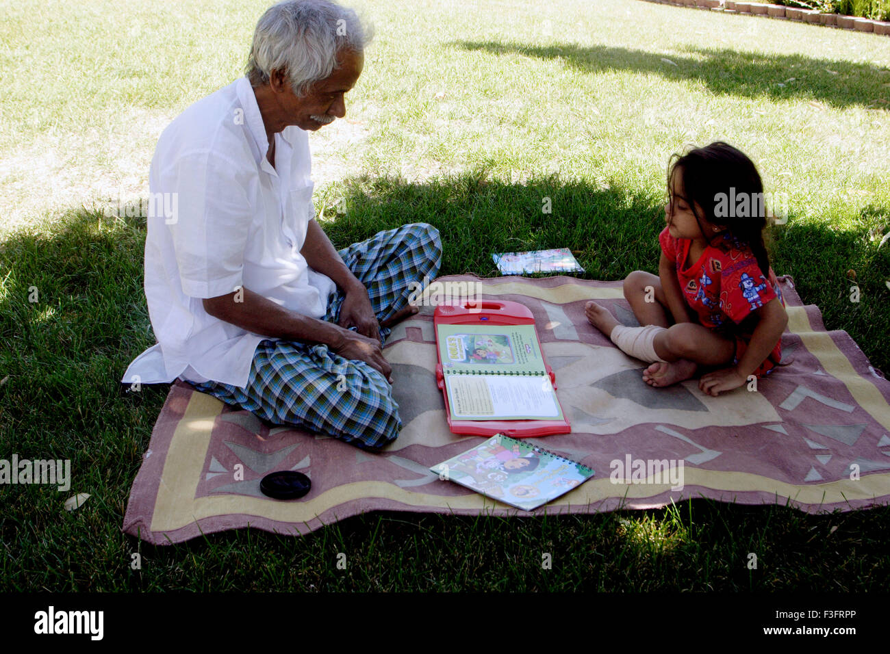 Grandfather reading story book and granddaughter listening - Stock Image