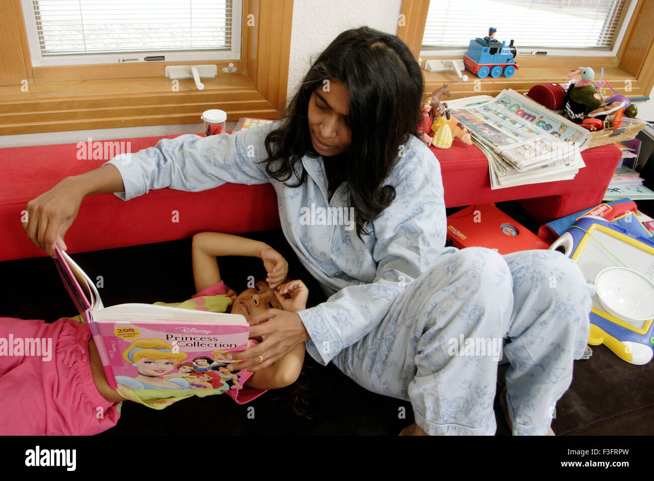Mother reading story book and daughter listening - Stock Image