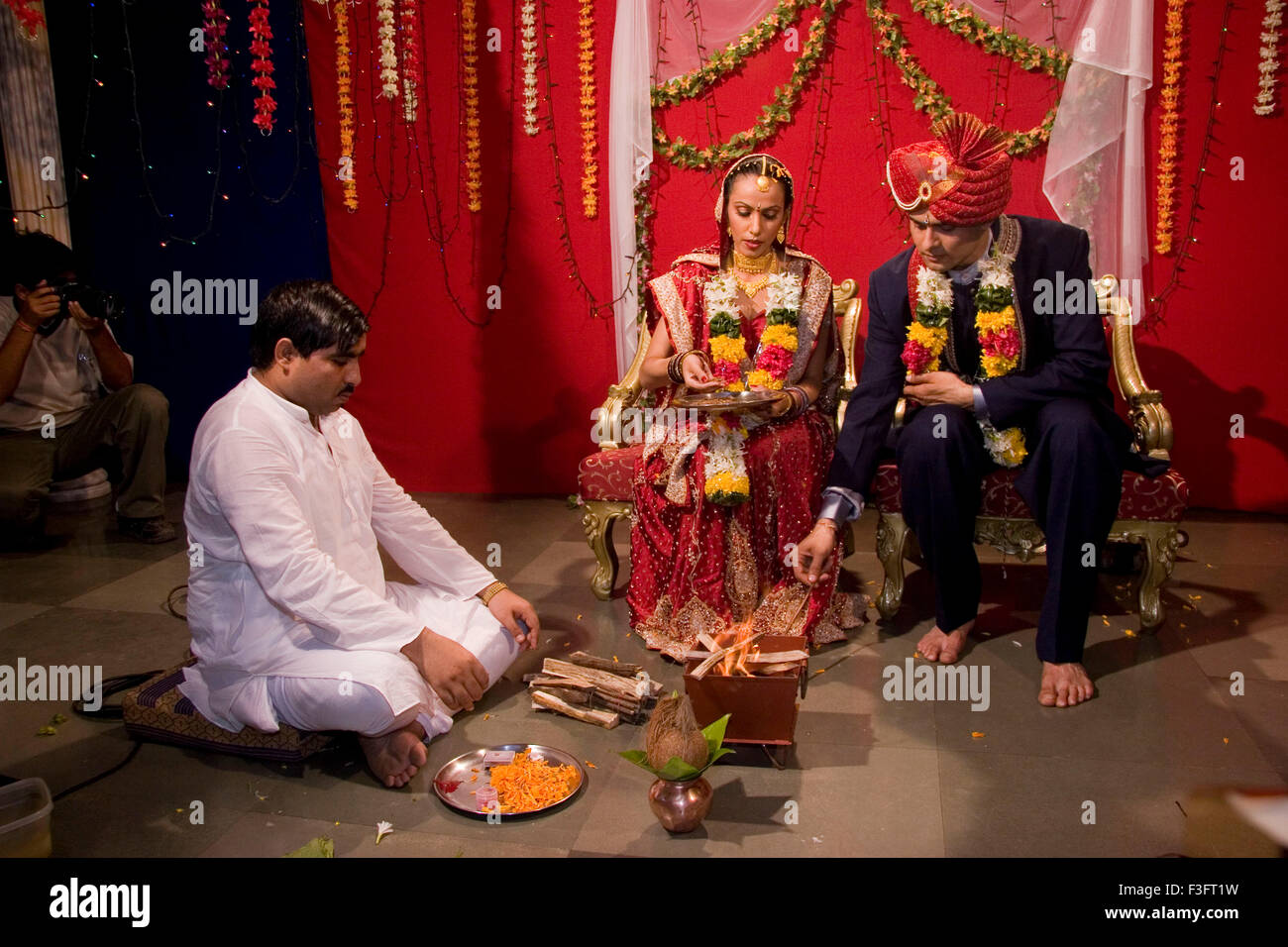 Pundit chanting mantra and bride and bridegroom offering in holy fire in marriage ceremony MR Bridegroom#729E;NO - Stock Image