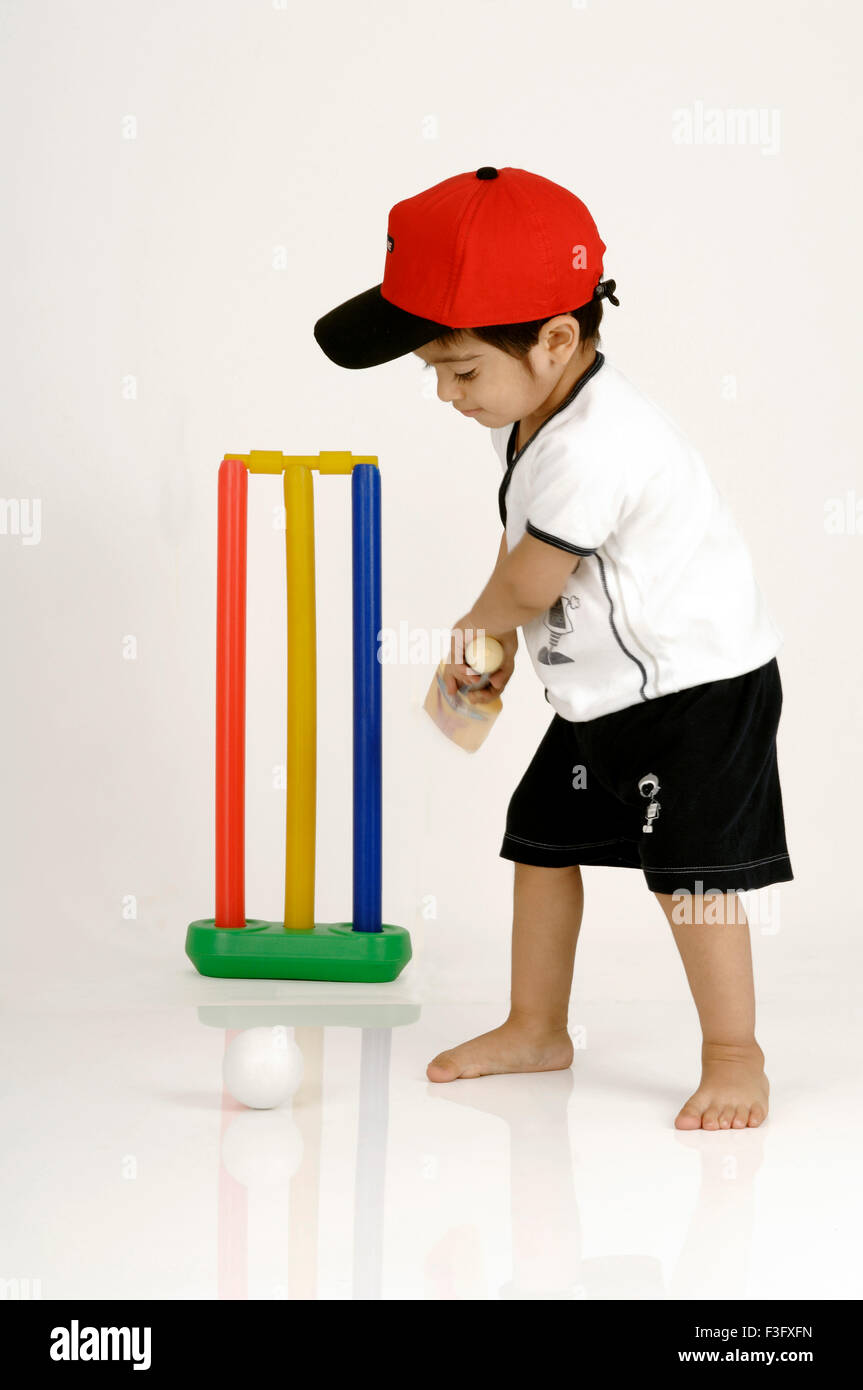 Indian Boy swinging the bat to hit the ball playing cricket ; MR - Stock Image