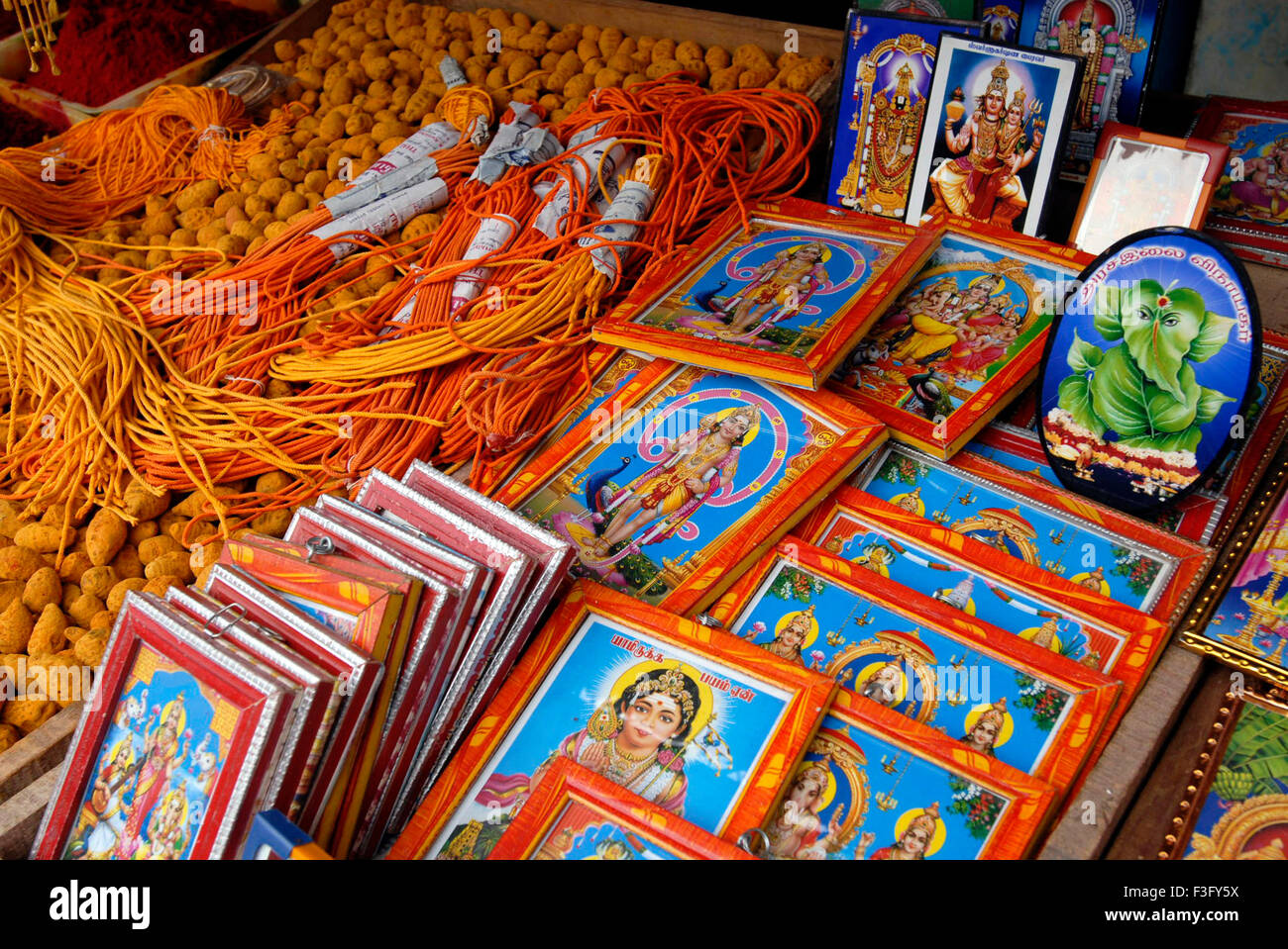 Turmeric and gods pictures in shop ; Swamimalai ; Tamil Nadu ; India Stock Photo