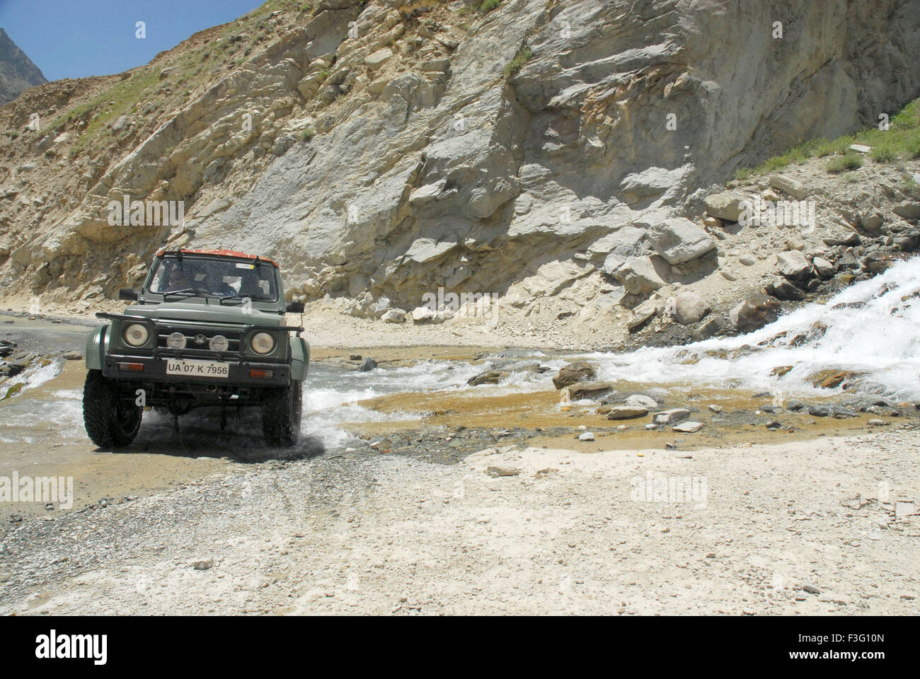 Car passing water in Bhaga valley ; Keylong ; Himachal Pradesh ; India - Stock Image