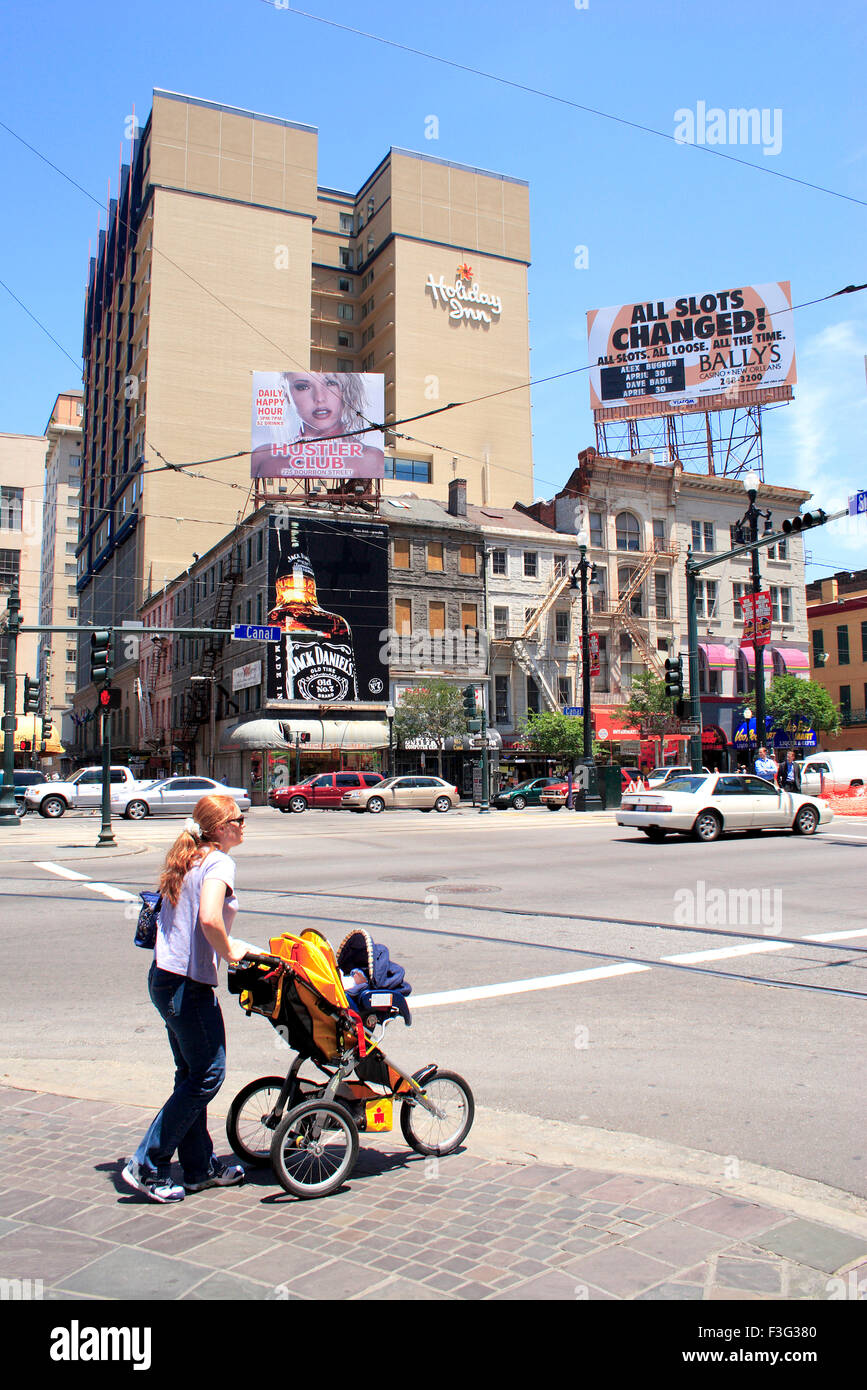 A lady carrying a baby in stroll ; Canal street; New Orleans ; Louisiana ; U.S.A. United States of America - Stock Image