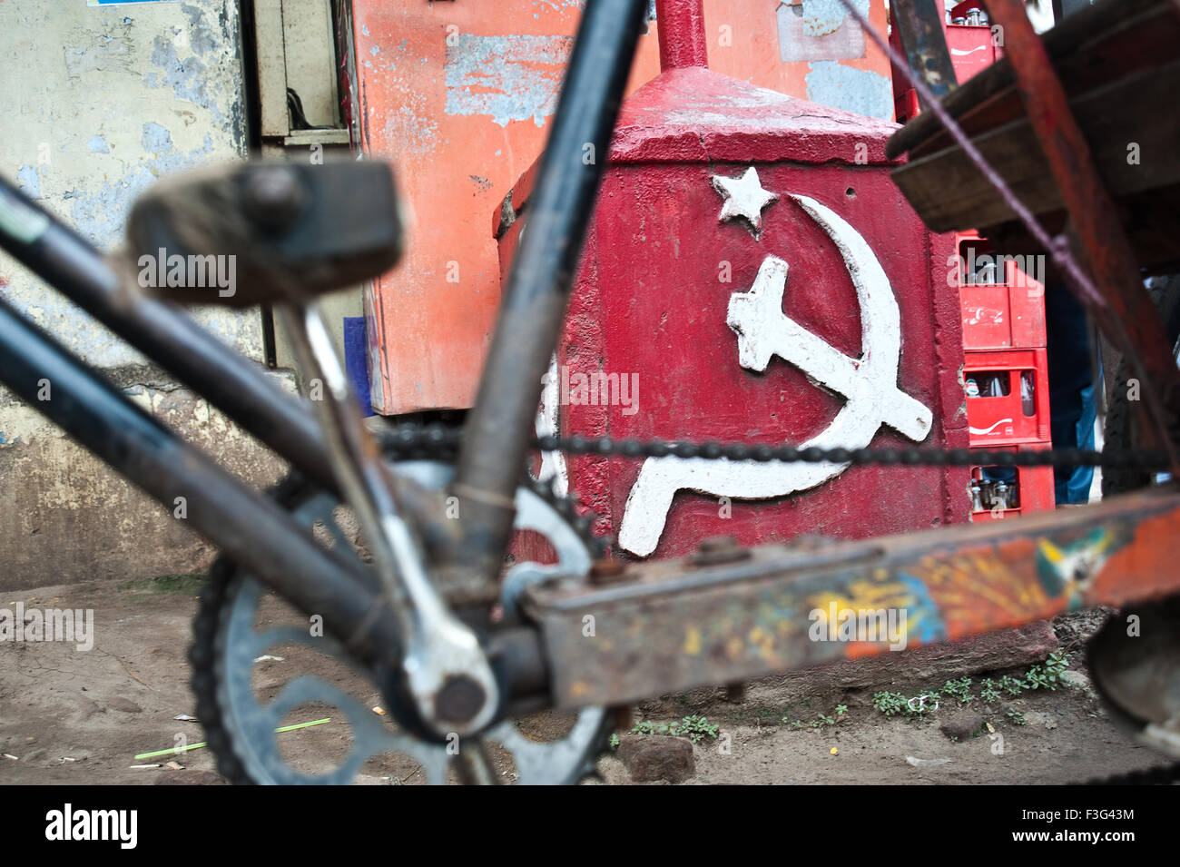 Communist symbol. In the foreground, crankset of a cycle rickshaw ( India) - Stock Image