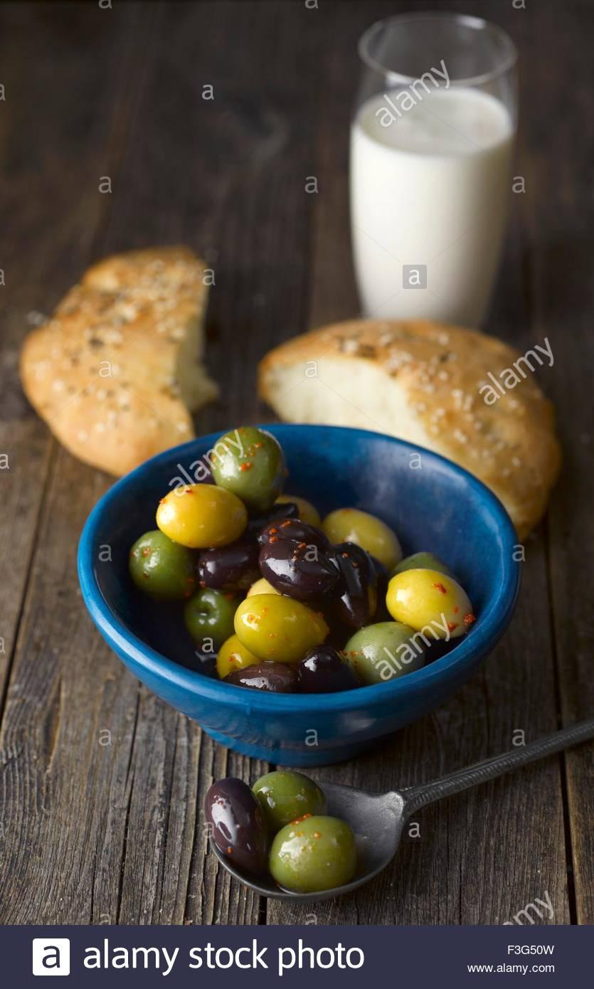 Unleavened bread with olives and Ayran (Turkish yogurt drink) - Stock Image