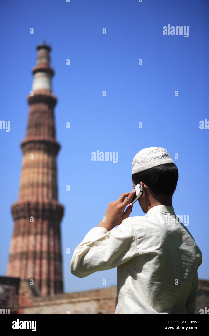 1e46a176ff4e Muslim boy talking on mobile phone at Qutab Minar built in 1311 red  sandstone tower