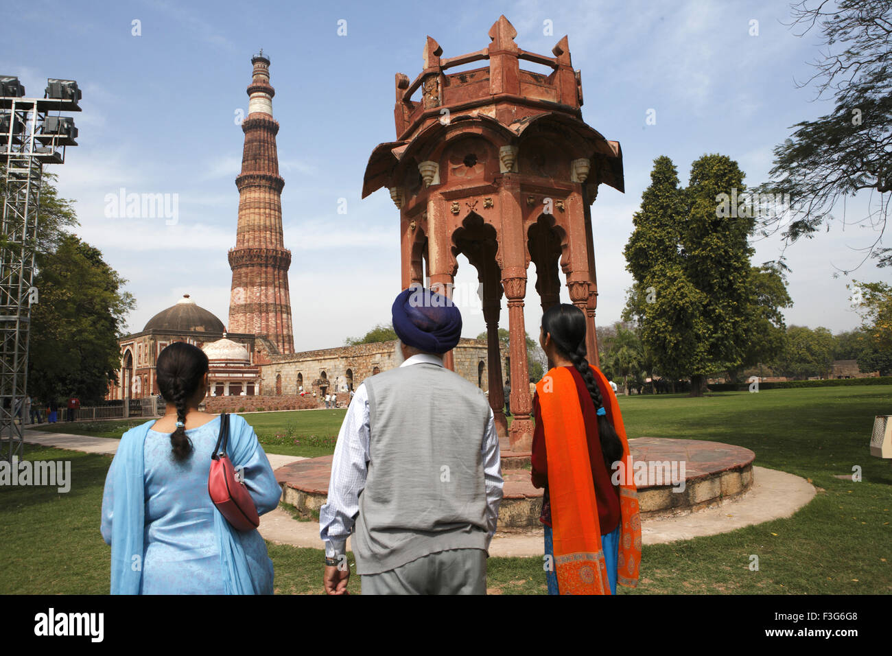 Punjabi Sikh family watching Smith's Folly and Qutb Minar built in 1311 red sandstone tower ; Indo Muslim art - Stock Image
