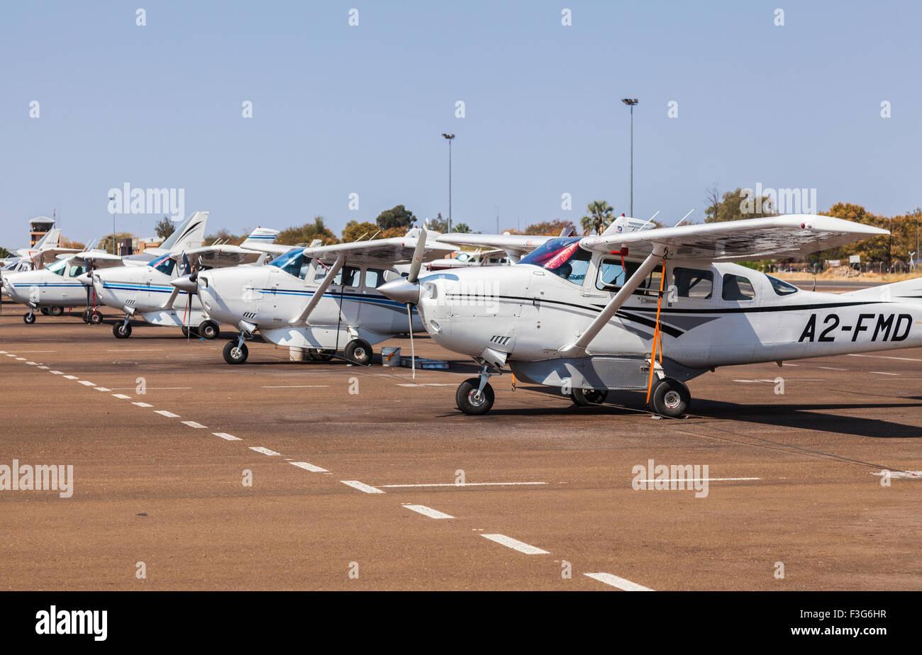 Air transport in the Okavango Delta: row of parked Mack Air Cessna 172 light aircraft at Maun Airport, Botswana, - Stock Image