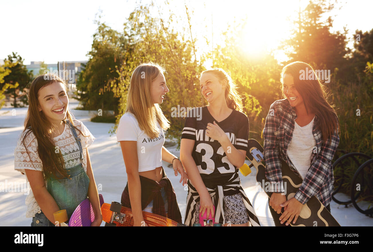 Four girls hanging out while talking and laughing Stock Photo