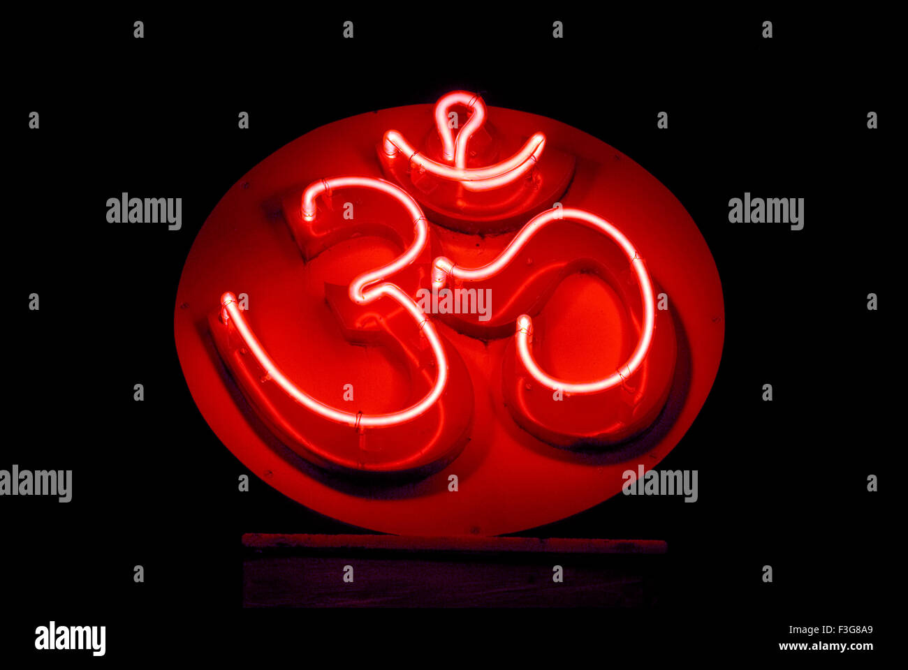 OM cosmic creation holy symbol of Hindu illuminated neon sign in red color - Stock Image