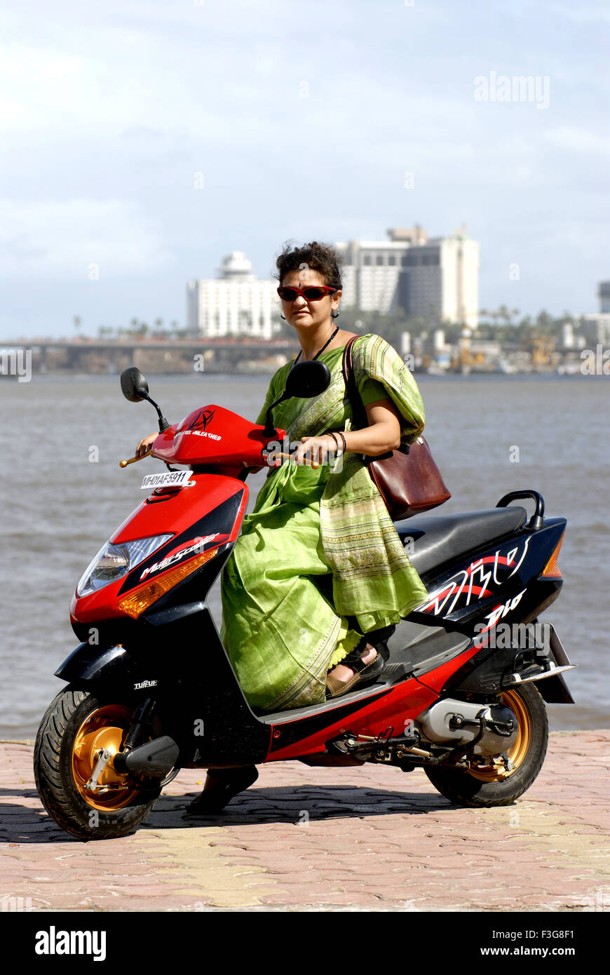 Working women driving Moto scooter ; Bombay now Mumbai ; Maharashtra ; India MR#721S - Stock Image
