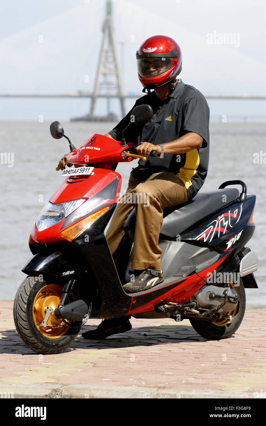 Man wearing helmet driving Moto scooter ; Bombay now Mumbai ; Maharashtra ; India - Stock Image