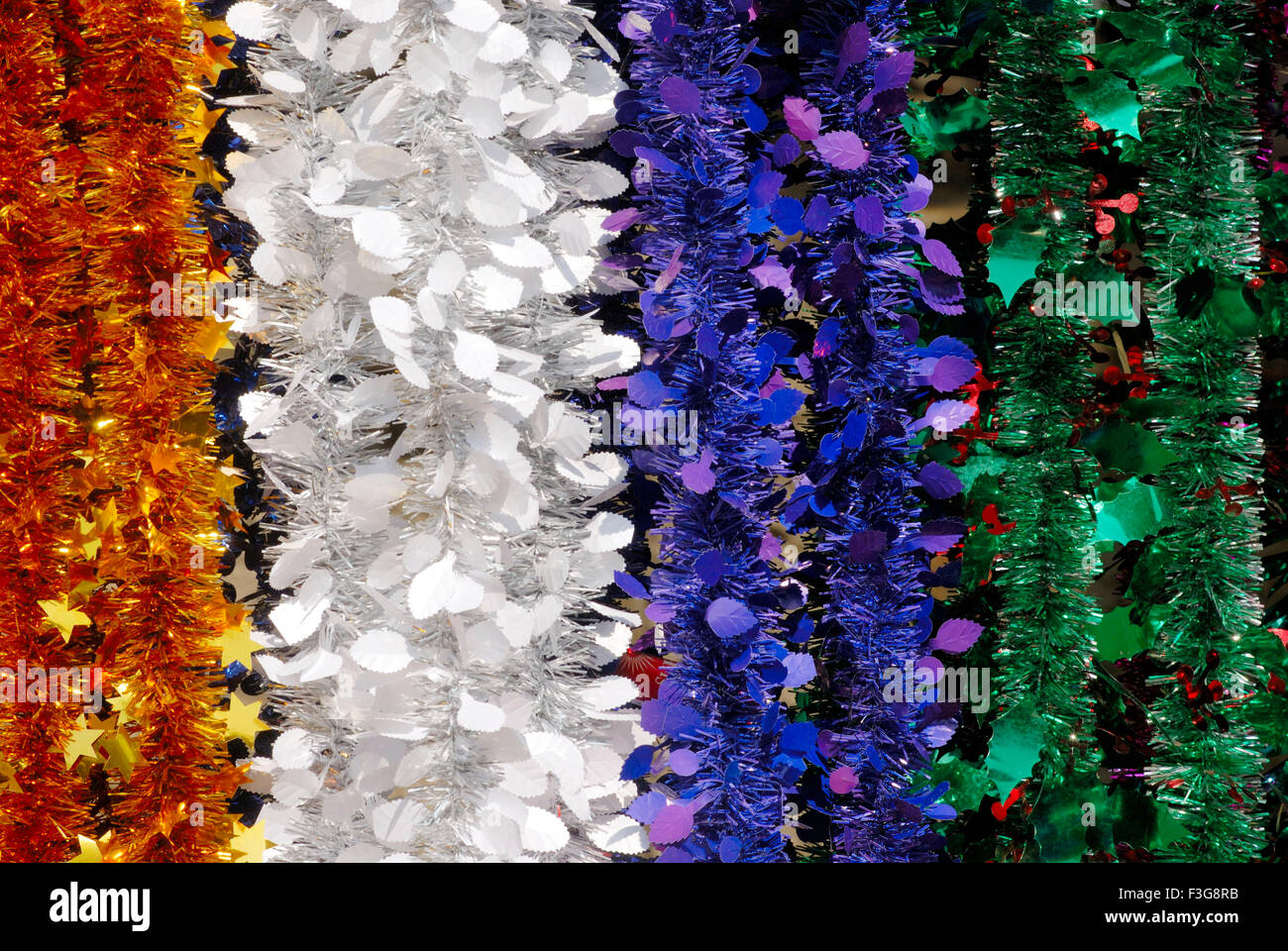 Long strings made colourful tinsel decorative material for celebrating Christmas Festival kept sell in shop Borivali - Stock Image