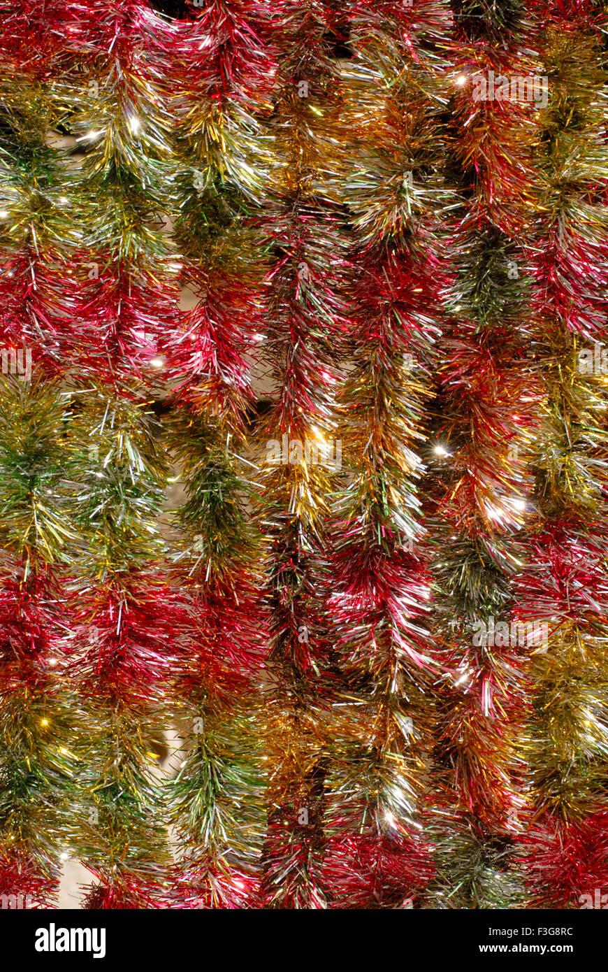 strings made colourful tinsel kept decorative material celebrating Christmas Festival kept sell shop Borivali Mumbai - Stock Image