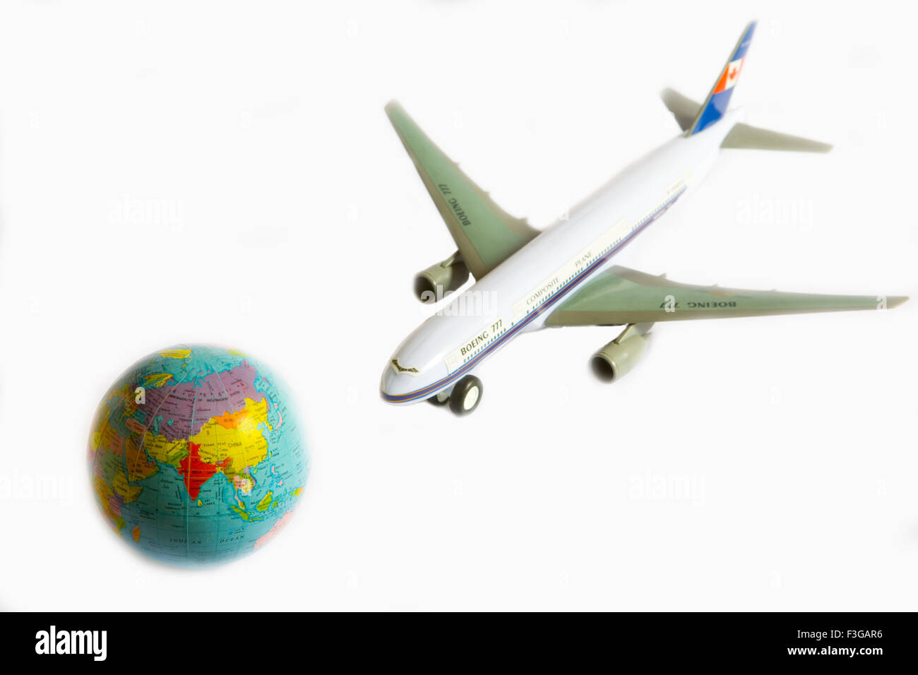 Toy aeroplane Boeing 777 and Globe on white background - Stock Image
