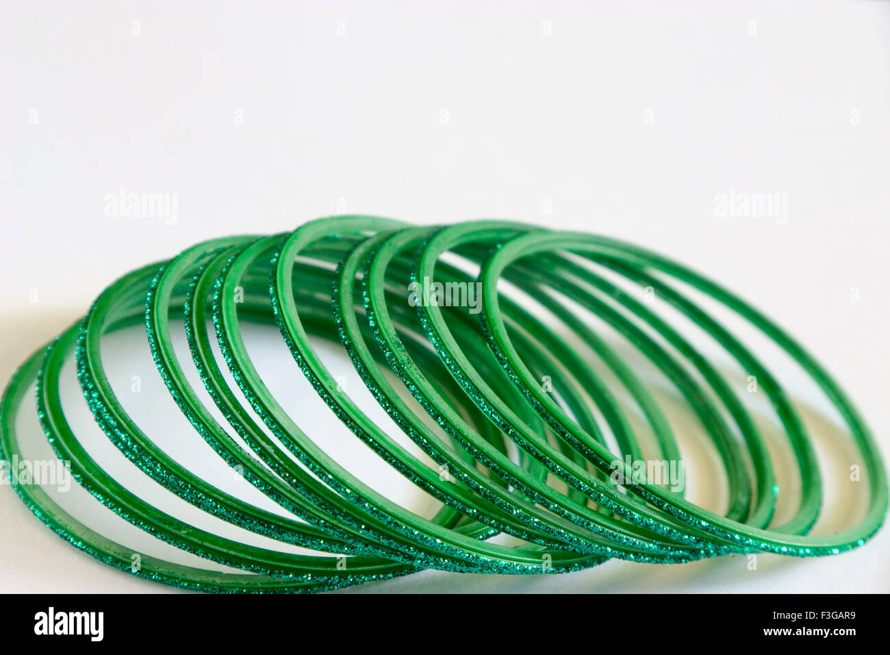 Eleven round green glass bangles on white background - Stock Image