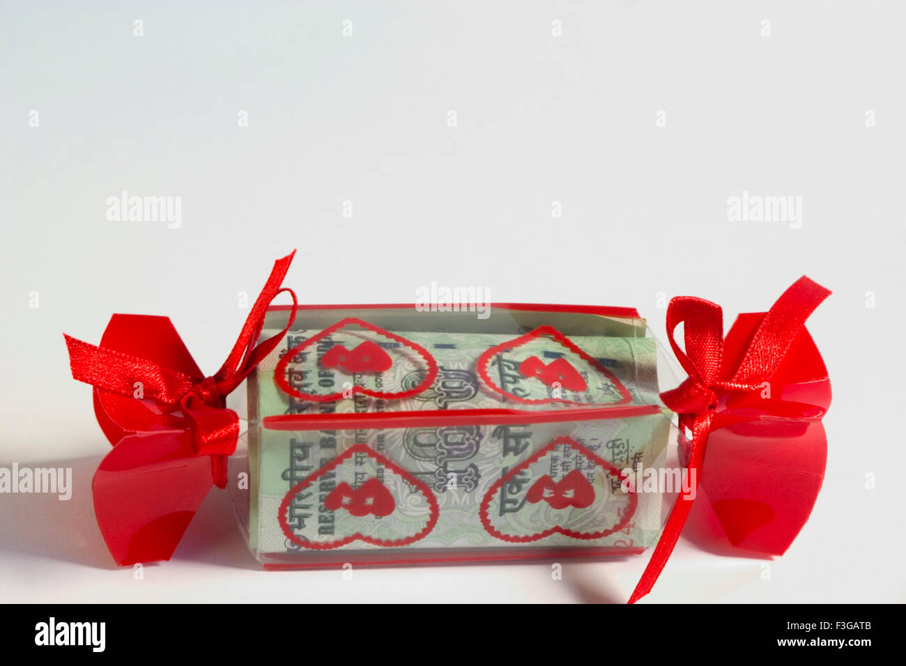 Concept ; hundred rupees Indian currency wrap in gift pack on white background Stock Photo