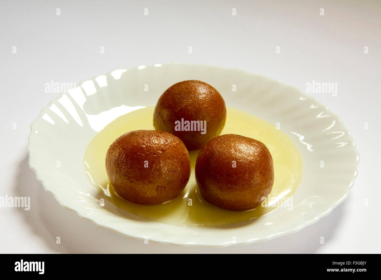 Indian sweet food three triple piece of round shape Gulabjamun Bonbon Confectionery with sugar syrup served in plate - Stock Image