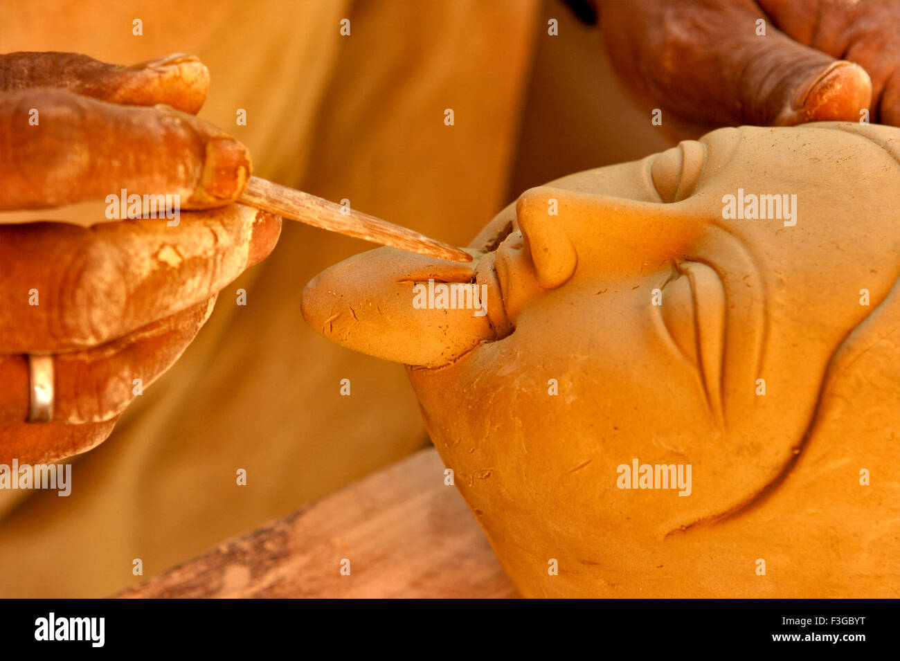 Sculptor giving finishing touches to Goddess Durga Kali sculpture made of clay for Durga Pooja Celebration ; Rajkot - Stock Image