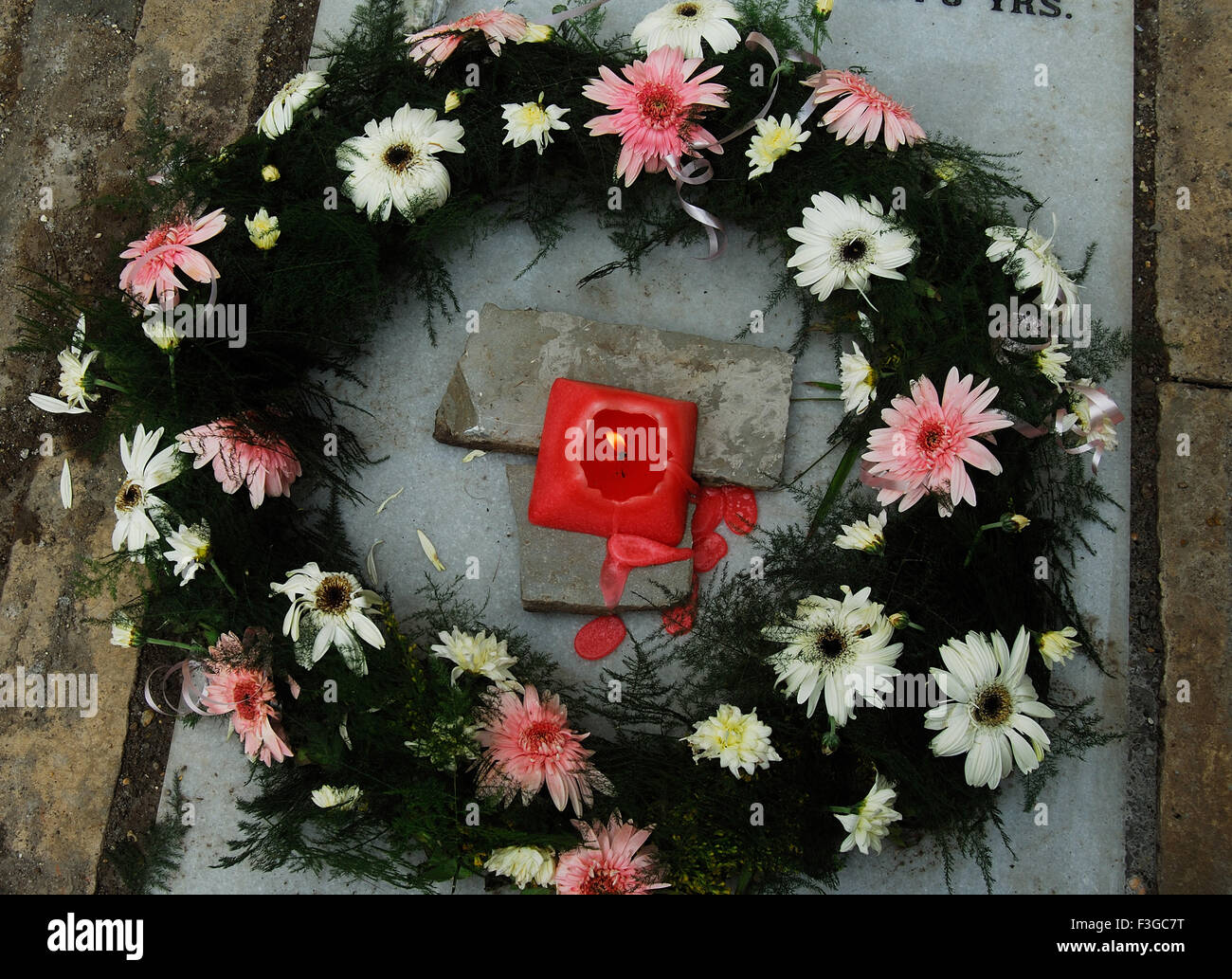 Floral And Candle On Grave for Tribute to the Departed Soul On The 2nd Day Of His Burial - Stock Image