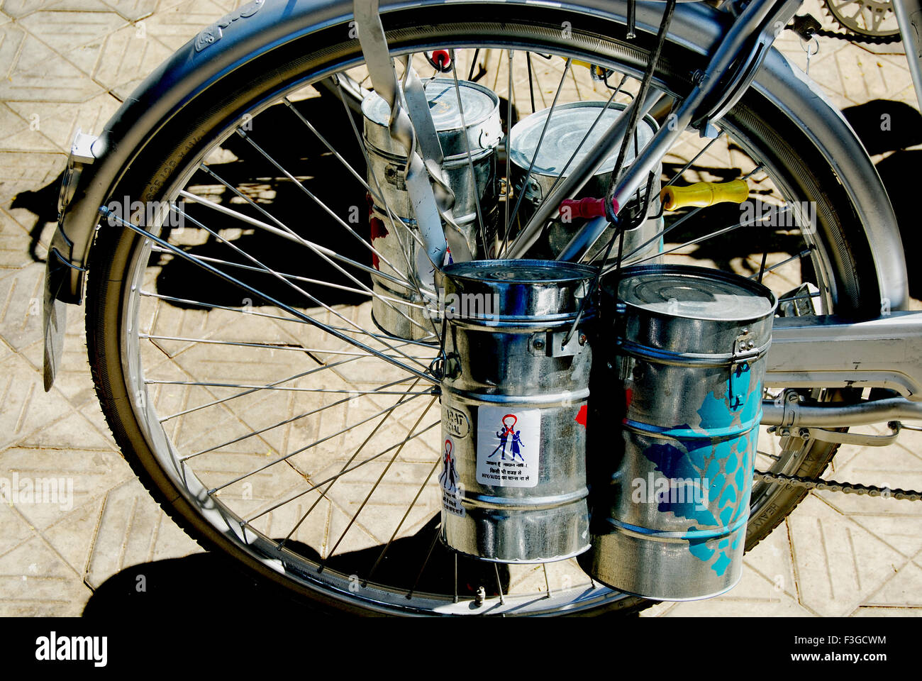 Food dabbas tied to rear wheel of cycle - Stock Image