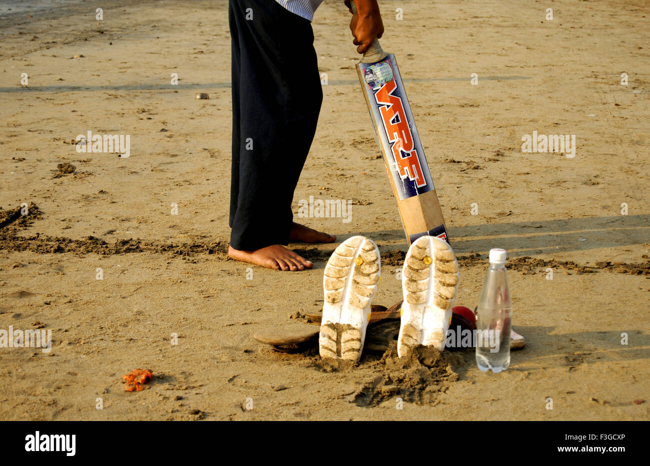 Cricket played by children at beach - Stock Image