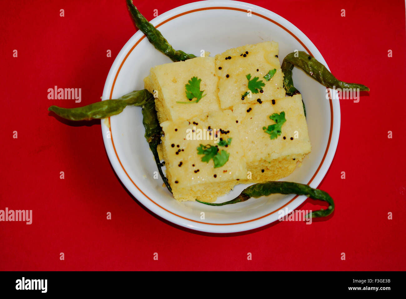 Four Pieces of Yellow Khaman or Dhoklas With Fried Green Chilies Served in Dish - Stock Image